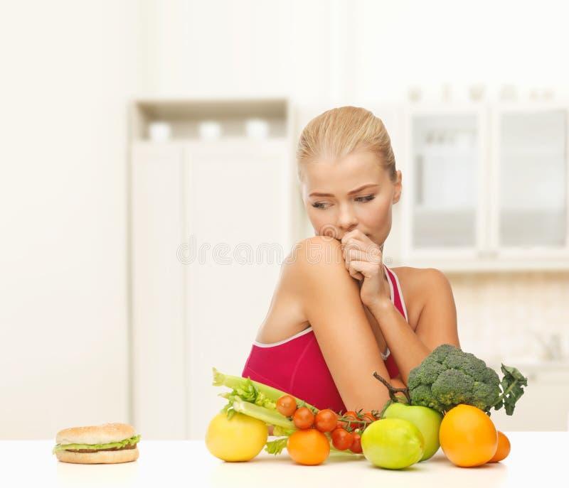 Douter de la femme avec les fruits et l'hamburger photo libre de droits