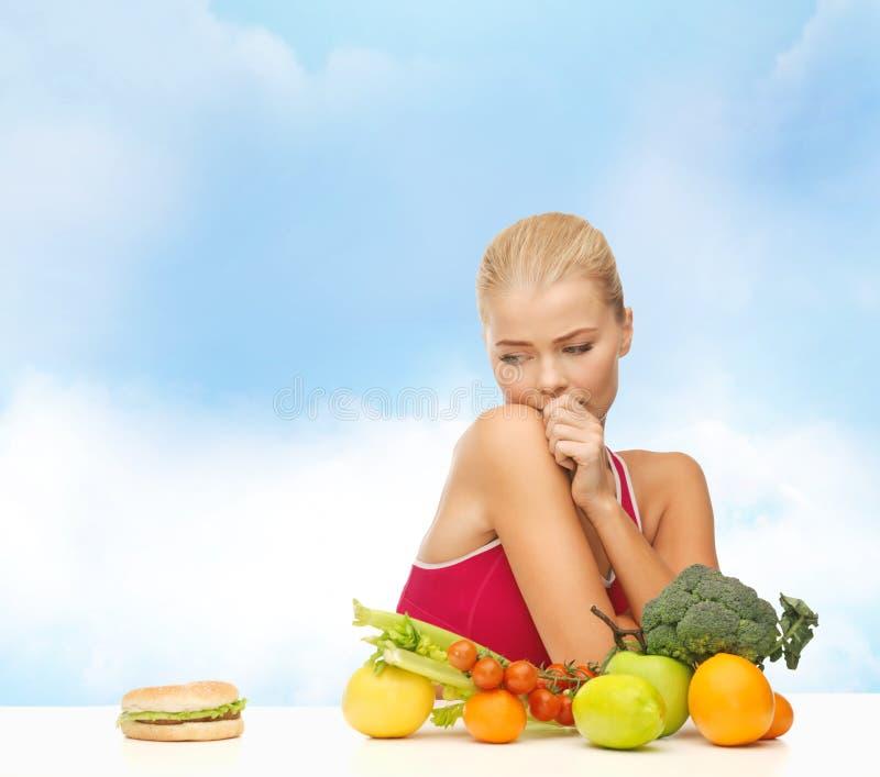 Douter de la femme avec les fruits et l'hamburger images stock