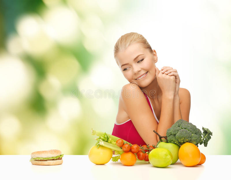 Douter de la femme avec les fruits et l'hamburger photos libres de droits