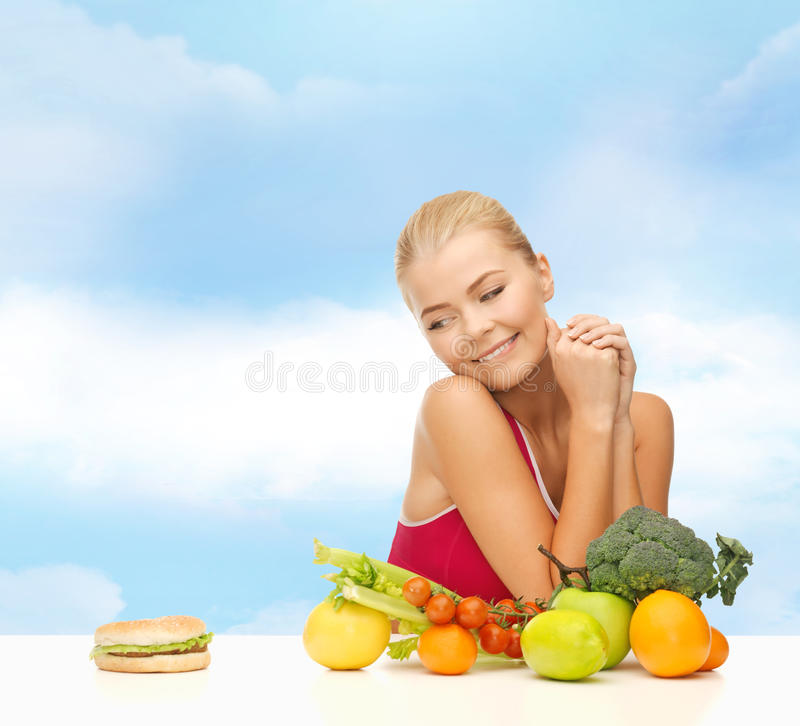 Douter de la femme avec les fruits et l'hamburger image libre de droits