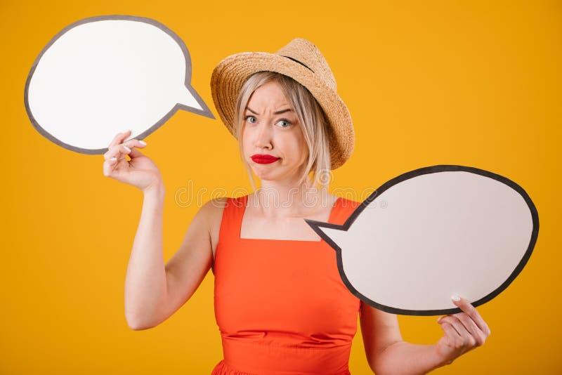 Douter de la femme bien choisie d'émotions dans le chapeau de paille et costumé rouge tient les bannières buble de la parole Fond images libres de droits