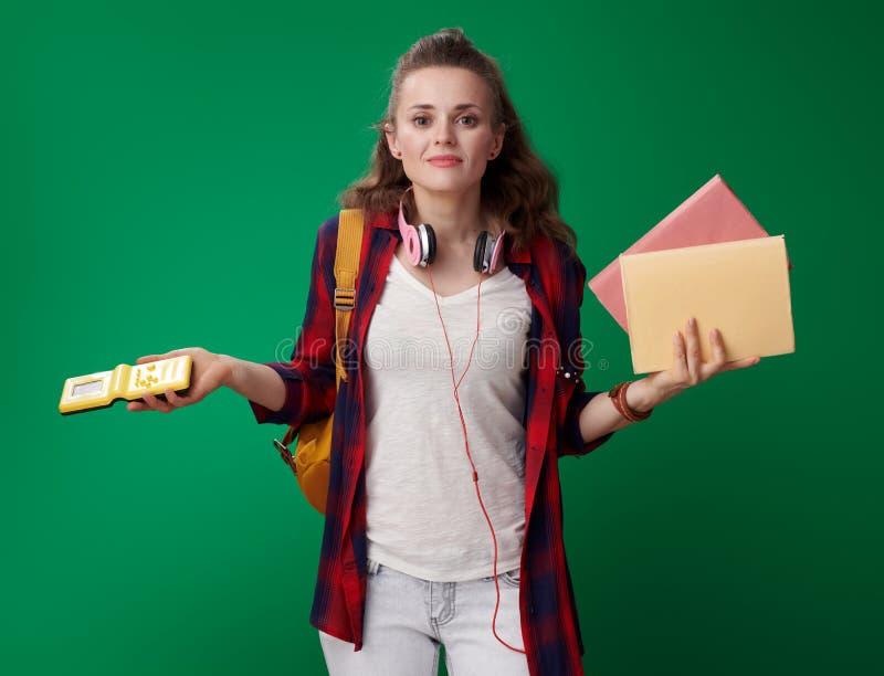 Douter de la femme d'étudiant choisissant entre les livres et le jeu vidéo images stock
