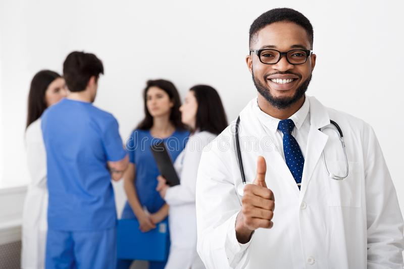 Doutor africano profissional Showing Thumb Up no hospital imagem de stock