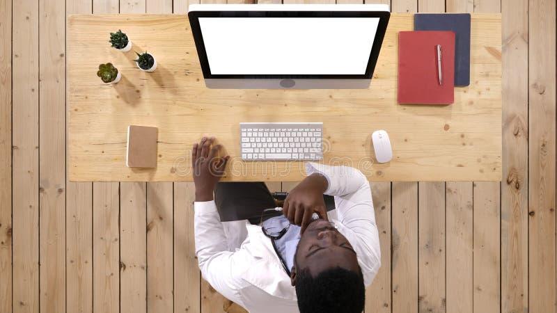 Doutor africano que olha algo na tela do computador Indicador branco imagens de stock