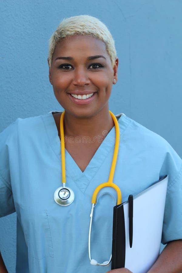 Doutor afro-americano feliz novo que está na divisão de hospital com prancheta e pena à disposição Sorriso, olhando a câmera imagens de stock royalty free