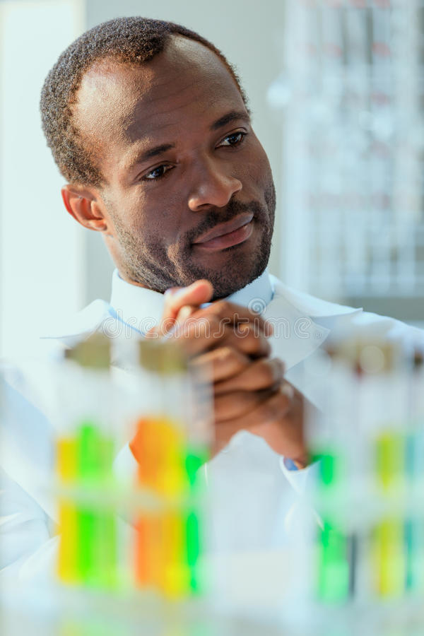 Doutor afro-americano no uniforme que senta-se no laboratório de testes foto de stock royalty free