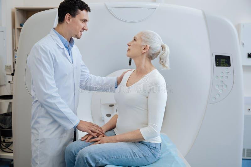 Doutor alegre considerável que diz a seu paciente um diagnóstico imagens de stock royalty free
