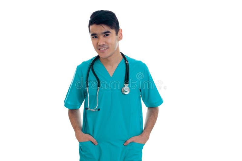 Doutor alegre do homem novo no uniforme azul com stethoscop em seu pescoço que levanta e que olha a câmera e o sorriso fotografia de stock