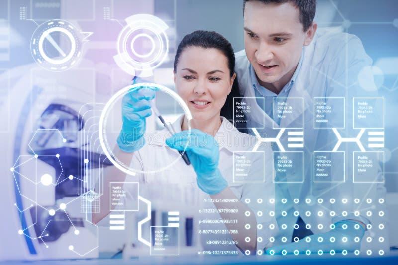 Doutor alegre que guarda amostras de sangue quando seu colega que está próximo fotografia de stock