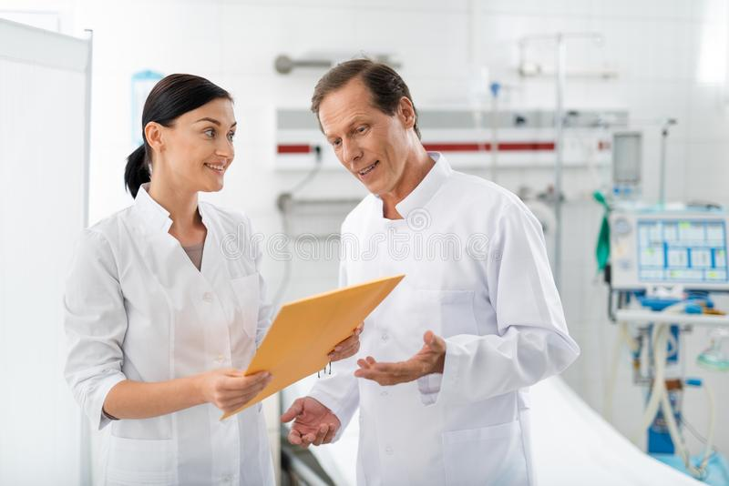 Doutor alegre que olha o envelope alaranjado nas mãos da enfermeira imagens de stock
