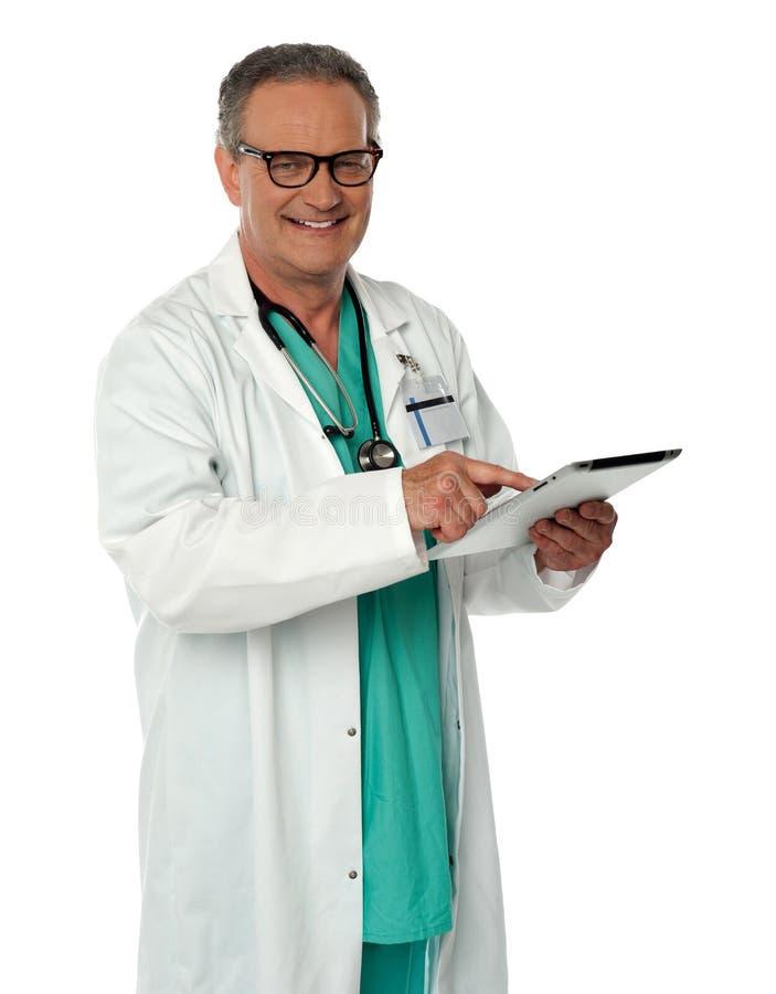 Doutor alegre que usa o dispositivo sem fio da tabuleta foto de stock