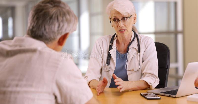 Doutor altamente educado que discute interesses da saúde com o homem idoso foto de stock