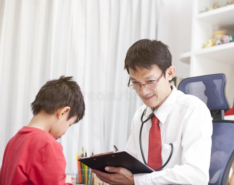 Doutor asiático do homem que toma a nota no papel da lista de verificação para um rapaz pequeno imagens de stock royalty free