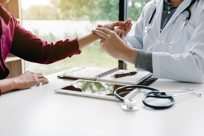 Doutor asiático masculino com as mãos da terra arrendada e o médico médico que tomam um pulso paciente na sala da clínica foto de stock royalty free
