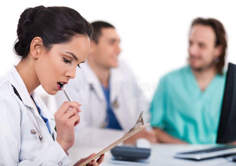 Doutor asiático novo que pensa com a pena fotos de stock