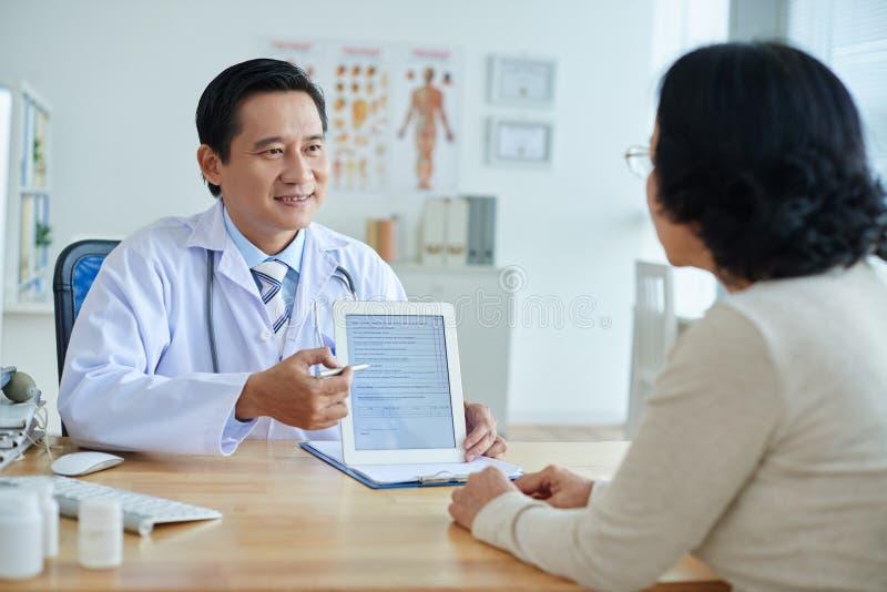 Doutor asiático que fala ao paciente fotografia de stock