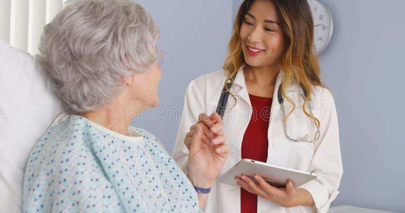 Doutor asiático que guarda a mão do paciente idoso da mulher no hospital fotos de stock royalty free