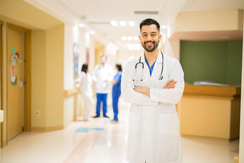 Doutor atrativo em um corredor do hospital fotografia de stock royalty free