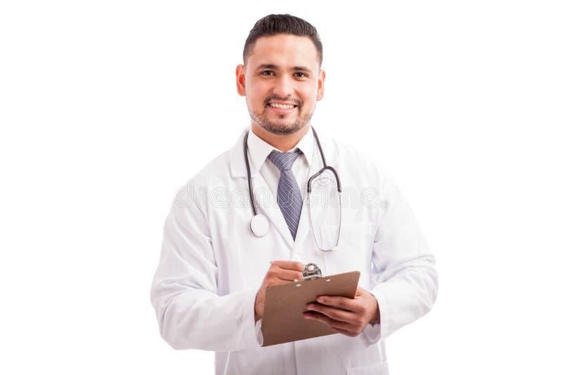Doutor atrativo que escreve uma prescrição fotos de stock