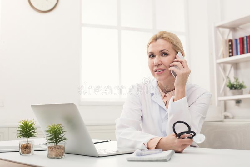 Doutor atrativo que fala no telefone com paciente foto de stock royalty free