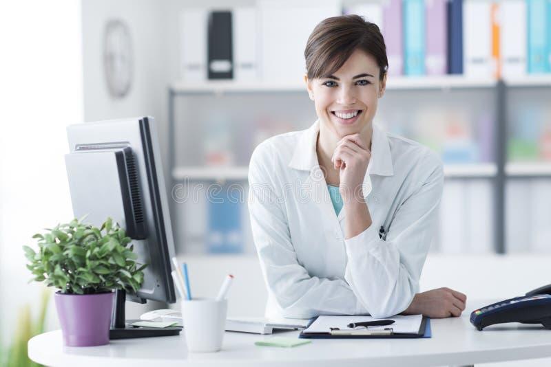 Doutor atrativo que levanta na recepção da clínica foto de stock royalty free