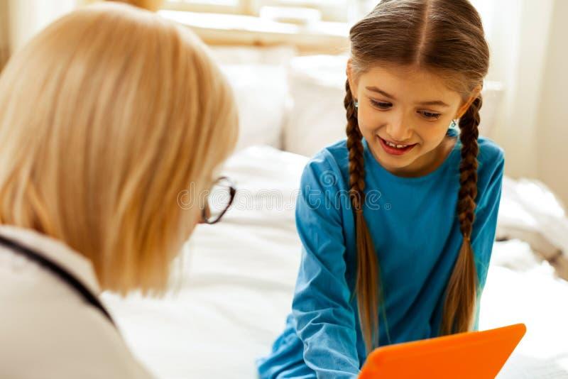 Doutor atrativo que oferece uma tabuleta a uma menina com tranças imagem de stock