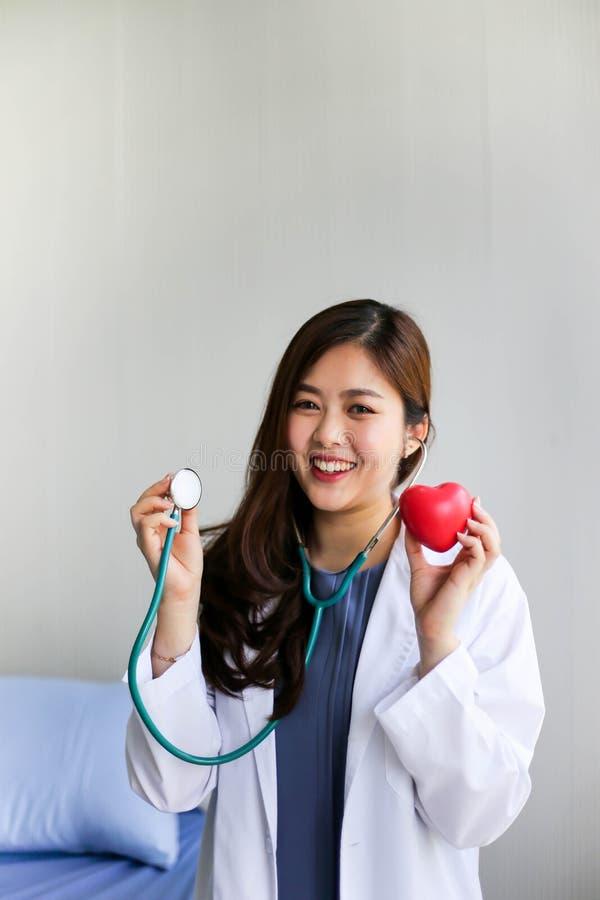 Doutor bonito da mulher com o estetoscópio que guarda o coração fotos de stock royalty free