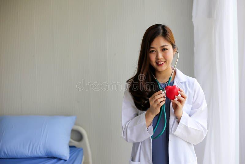 Doutor bonito da mulher com o estetoscópio que guarda o coração imagem de stock