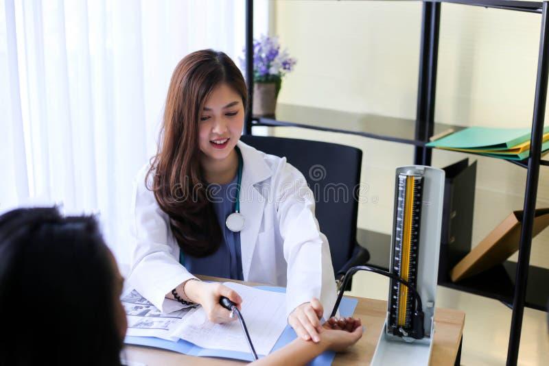 Doutor bonito da mulher que verifica uma pressão sanguínea dos pacientes fotos de stock