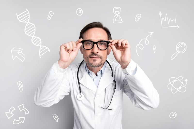 Doutor calmo que toca em seus vidros e que olha atento fotos de stock royalty free