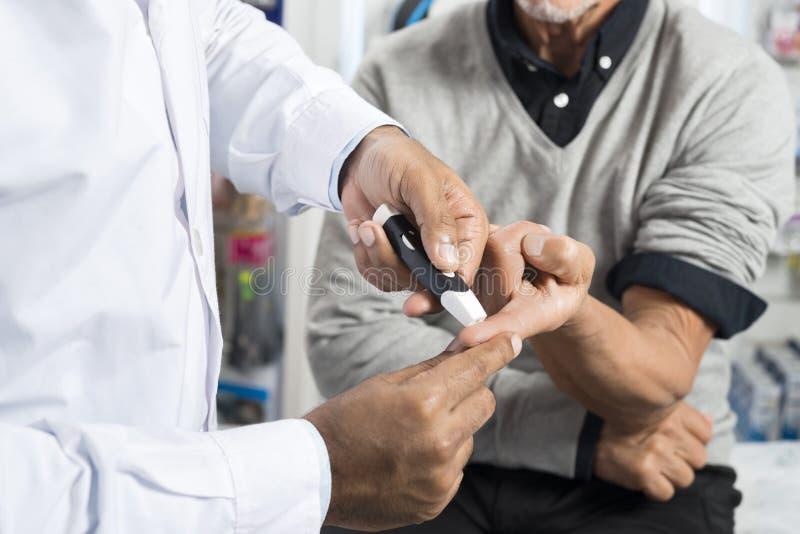 Doutor Checking Sugar Level Of Senior Patient com Glucometer foto de stock