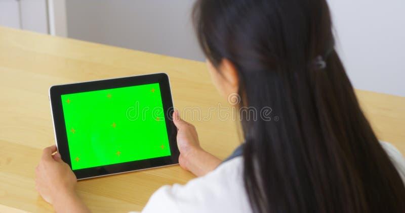 Doutor chinês que fala à tabuleta com tela verde fotos de stock