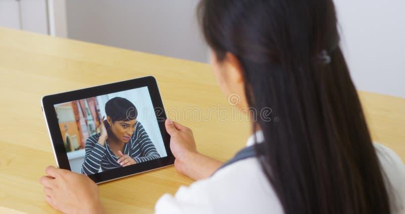 Doutor chinês que fala com o paciente da jovem mulher na tabuleta imagem de stock royalty free
