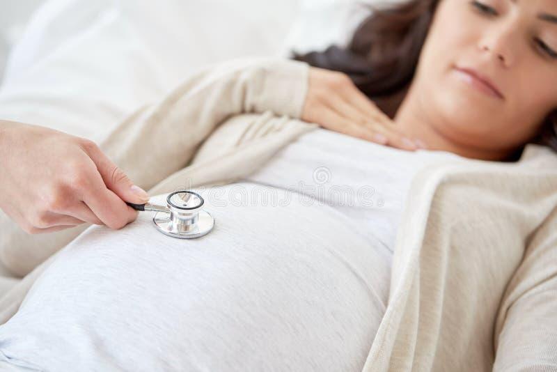Doutor com estetoscópio e mulher gravida imagens de stock royalty free