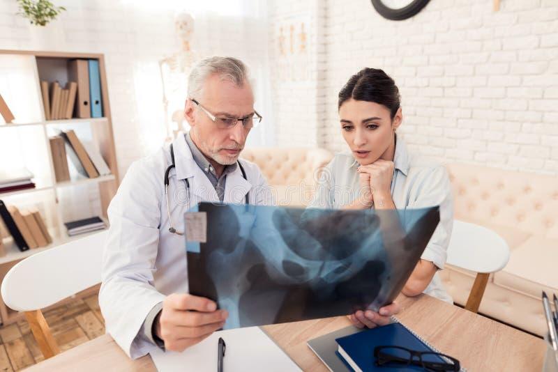 Doutor com estetoscópio e o paciente fêmea no escritório O doutor está mostrando o raio X ao paciente imagens de stock