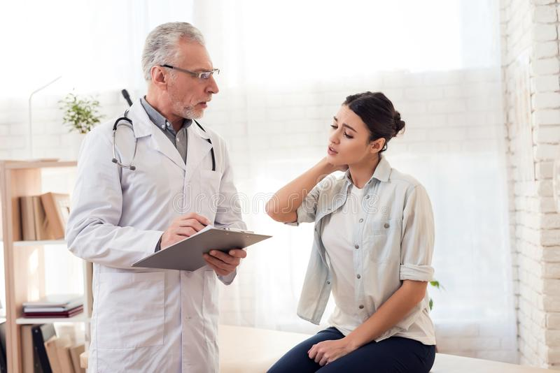 Doutor com estetoscópio e o paciente fêmea no escritório Os danos pacientes do pescoço do ` s fotos de stock
