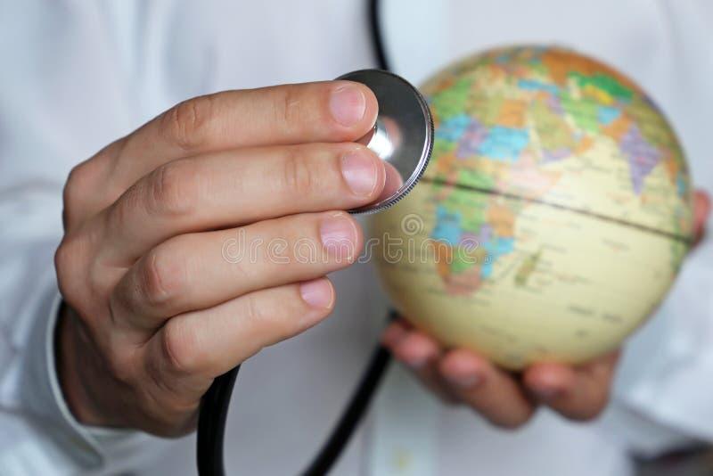 Doutor com estetoscópio e um globo em suas mãos fotografia de stock royalty free