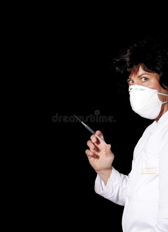Doutor com máscara cirúrgica e seringa fotos de stock royalty free