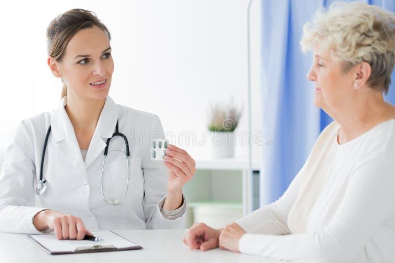 Doutor com o estetoscópio que dá comprimidos fotografia de stock