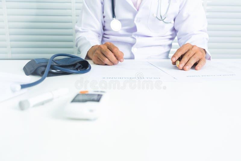 Doutor com o monitor da frequência cardíaca e o monitor da glicemia fotografia de stock