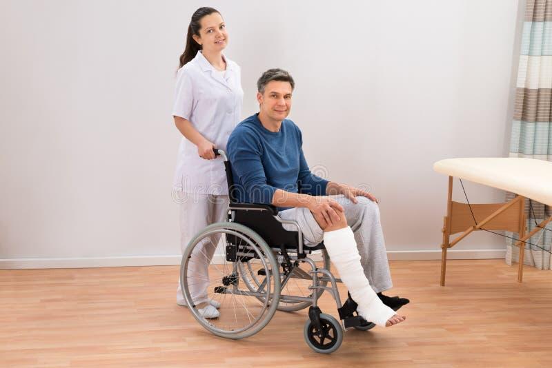 Doutor com o paciente deficiente na cadeira de rodas fotografia de stock