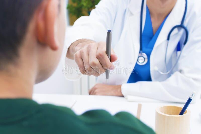 Doutor com a pena a assinar fotografia de stock