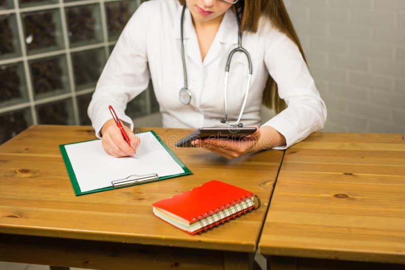 Doutor com tabuleta digital Doutor fêmea novo atrativo no revestimento branco do laboratório que trabalha na tabuleta digital foto de stock royalty free