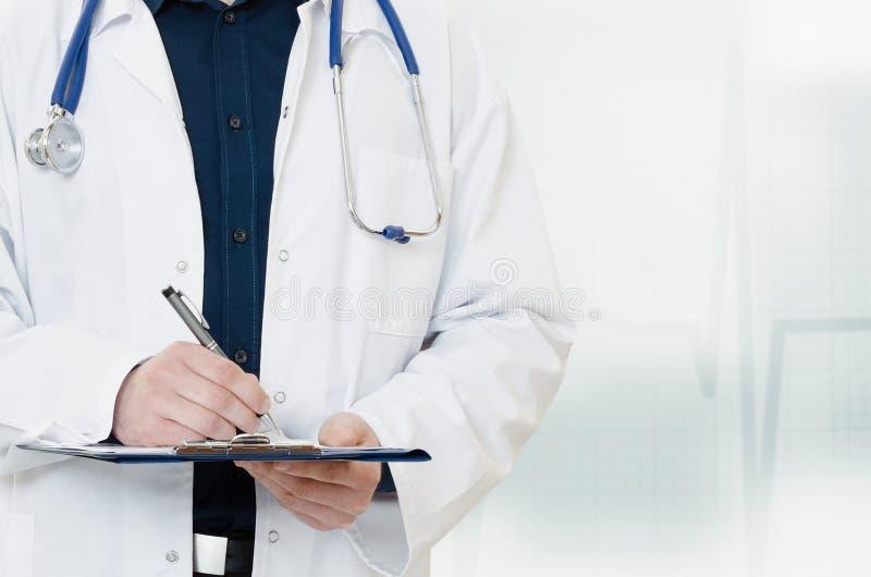 Doutor com um estetoscópio, guardando um caderno em sua mão imagem de stock