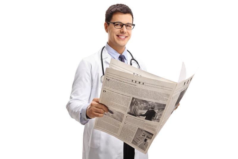 Doutor com um jornal que olha a câmera e o sorriso imagem de stock