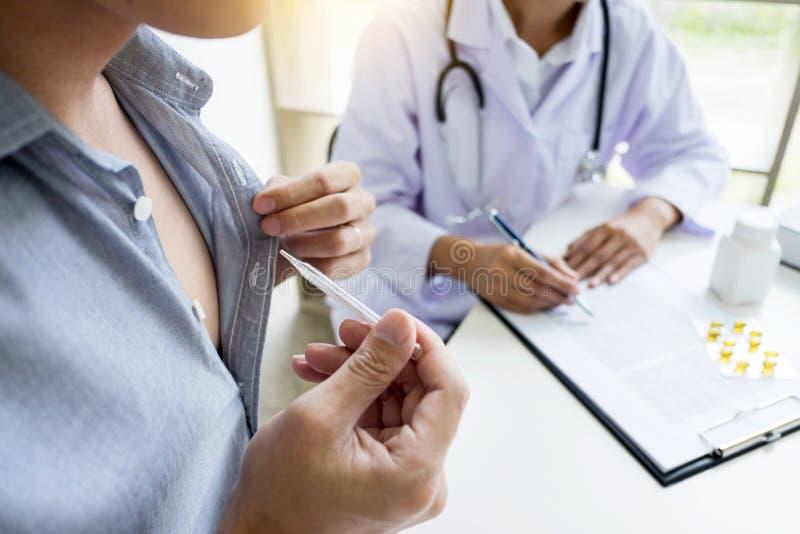 Doutor com um termômetro em sua mão que toma o ` paciente s no hospit foto de stock royalty free