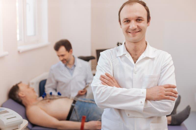 Doutor competente novo que ajuda a seu cardiologista companheiro fotos de stock