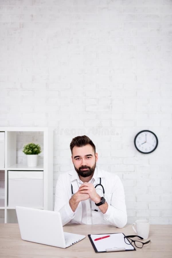 Doutor considerável do homem que usa o portátil no escritório - espaço da cópia sobre a parede de tijolo branca foto de stock royalty free