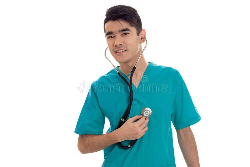 Doutor considerável novo do homem que levanta com o estetoscópio no uniforme isolado no fundo branco no estúdio foto de stock