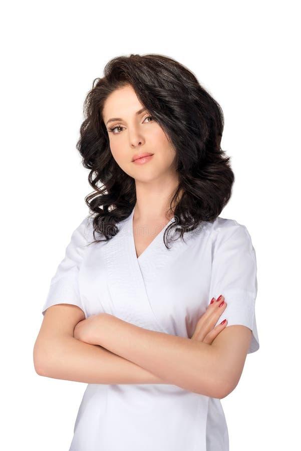 Doutor consideravelmente fêmea dos jovens no uniforme que mantém os braços cruzados e que olha a câmera isolada no fundo branco fotos de stock